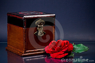Wooden casket and red flower on blue