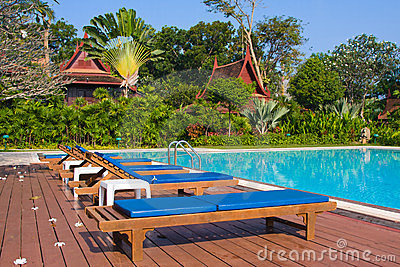 Wooden chaise lounges on the bank of pool.