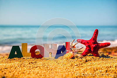 Wooden colorful word  Aloha  on the sand