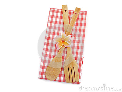 Wooden cooking utensils with red checkered cloth isolated on white
