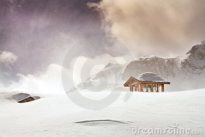 Wooden cottage and snow covered huts in blizard