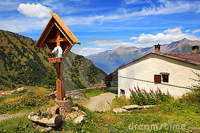 Wooden cross near rural house in Alps.