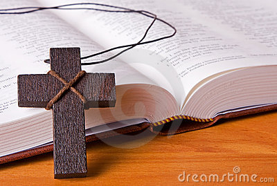 A wooden cross resting against a bible