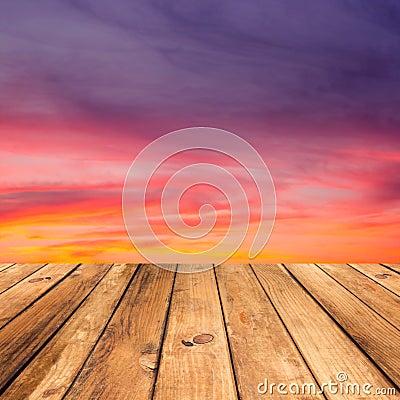 Wooden deck floor over beautiful sunset background.