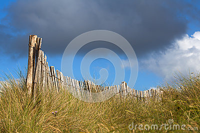 Wooden fence on the dunes with vivid clouded sky