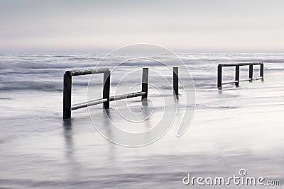 Wooden fence insea waterat sunset