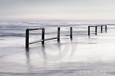 Wooden fence in sea water at sunset