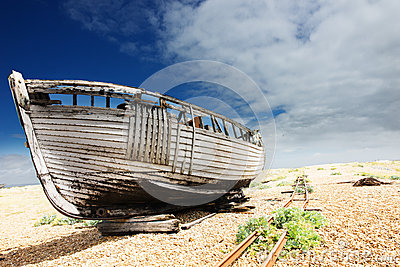 Wooden fishing boat left to rot and decay on the shingle beach at Dungeness, England, UK.
