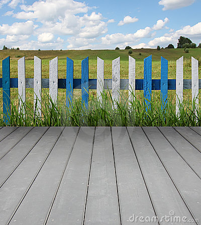 Wooden floor with fence and green grass