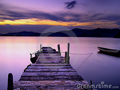 Wooden Foot Bridge and small boat at Sunset