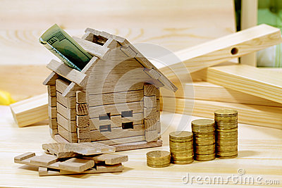 Wooden house block with coins finance property and for Loan to buy land and build house
