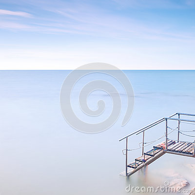 Wooden ladder pier to sea water. Long exposure.