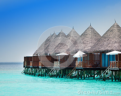 Wooden lodges on a beach at water
