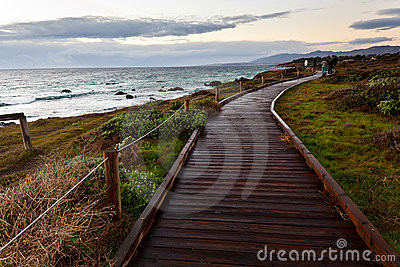 Wooden path along side the sea at sunset