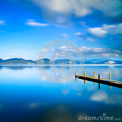 Wooden pier or jetty and on a blue lake sunset and sky reflection on water. Versilia Tuscany, Italy