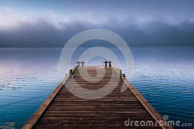 Wooden pier near fog cloud in morning river