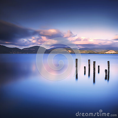 Free Wooden Pier Or Jetty Remains On A Blue Lake Sunset And Sky Refle Royalty Free Stock Images - 64896939