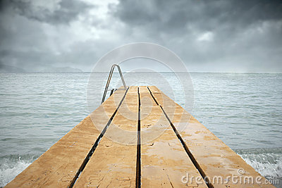 Wooden pier with sea in a gloomy day