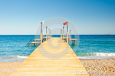 Wooden pier stretching into the sea, shot at dawn