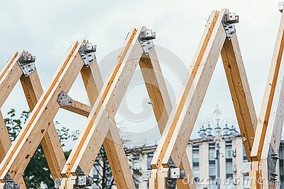 Wooden rafters of unfinished roof against the background of the city and white sky. The concept of building and creating. New housing royalty free stock image