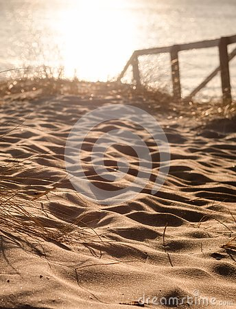 A wooden road among the dunes leading to the Baltic Sea at sunset in Klaipeda, Lithuania Stock Photo