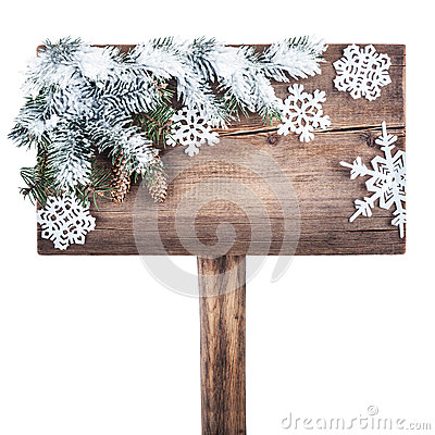 Wooden road sign with Christmas tree in the snow