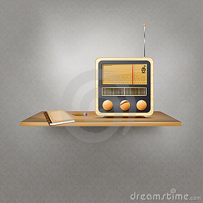 Wooden shelf with vintage radio, book and pencil
