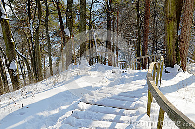 Wooden snowy oak staircase handrail steep hill
