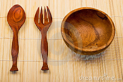 Wooden spoon, fork and basi on bamboo mat