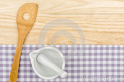 Wooden spoon and mortar on a purple checkered table cloth
