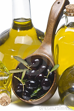 Wooden spoon, olives and bottles of oil.
