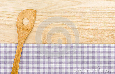 Wooden spoon on a purple checkered table cloth