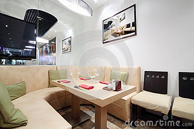 Wooden table, beige leather sofa in cozy restaurant