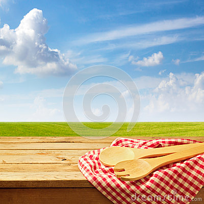 Free Wooden Table With Kitchen Utensil Over Green Meadow And Blue Sky Stock Photo - 46266340