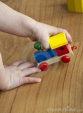 Free Wooden Train In Hands Of A Baby Royalty Free Stock Image - 14262246