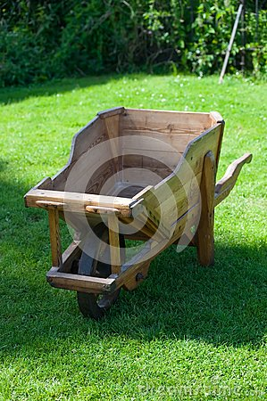 Wooden trolley on green grass in the garden