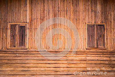 Wooden wall of ancient house with window closed.