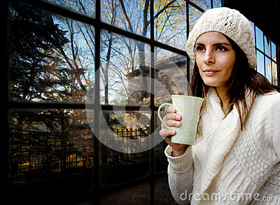 Wool dressed girl with mug against glass wall