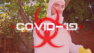 Word Covid-19 written over health hazard sign with a man dressed in protective suit in background. Animation of the word Covid-19 written in white over health stock video footage