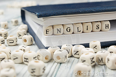 Word english made with block wood letters next to a pile of other letter over wooden table Stock Photo