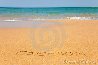 The word Freedom written on the beach sand