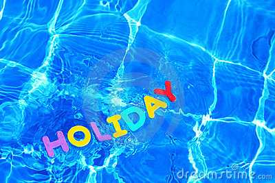 Word HOLIDAY floating in a swimming pool