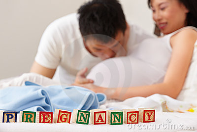 Word pregnancy in front of happy couple