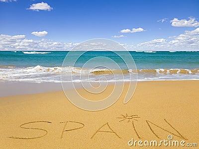 The word Spain written on the beach sand