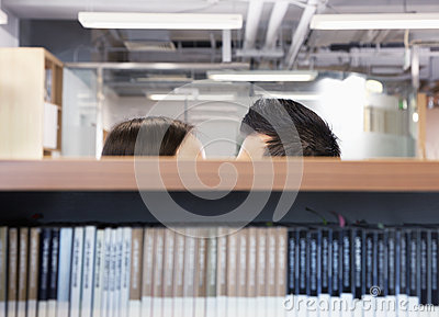 Work romance between two business people hiding behind shelves