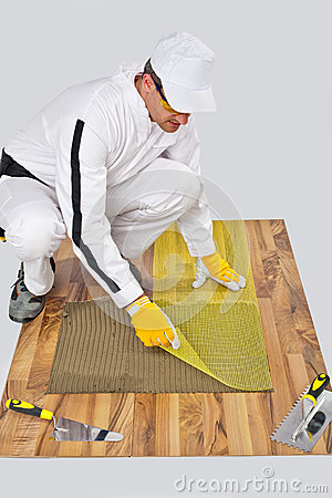 Worker applies fiber mesh on tile adhesive
