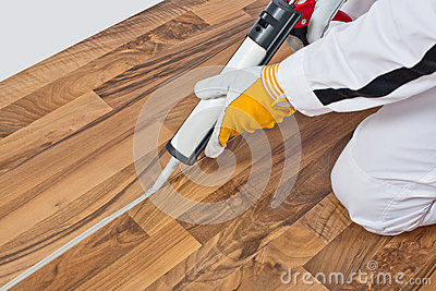 Worker applies silicone sealant on wooden floor