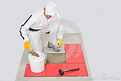 Worker Applies Tile Adhesive with Notched Trowel