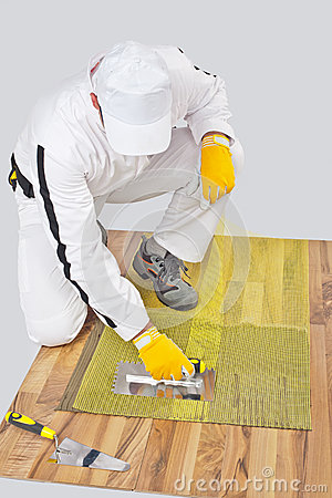 Worker applies tile adhesive on wooden floor