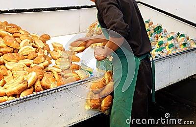 Worker in a bakery packaging bread